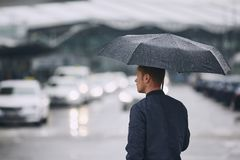 Rain in city. Young man holding umbrella walking in the street royalty free stock image