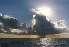 Rain cloud and shower over the ocean. An Isolated rain cloud and shower over the ocean Stock Image