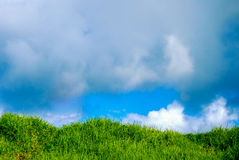 Rain Clouds Over Grass Knoll. The vivid green of the grassy knoll and the bright  blue of the sunny sky in the background are threatened by the appearance of Stock Photography