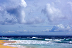 Rain clouds above Beach. Rain clouds gather at mid day above tropical paradise of Sandy Beach, Oahu. The dark clouds turn the turquoise waters a deep blue Stock Images