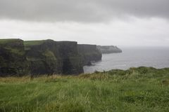 Raining at the Cliffs of Moher. Rain and clouds add mysterious views at the Cliffs. Folks climb the steep hills to get a better view royalty free stock photos