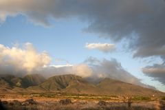 Clouds Over West Maui Mountains in Hawaii. Rain clouds disperse at the sun set on the West Maui Mountains royalty free stock images