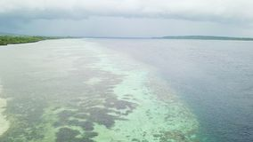 Rain Clouds Drift Over a Coral Reef in Wakatobi. A beautiful coral reef grows off an island in Wakatobi National Park in Indonesia. This region harbors extremely stock video