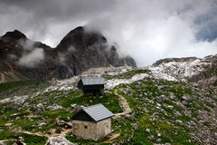 Rain clouds over huts in Triglav Lakes Valley, Julian Alps. Rain clouds over Triglav Lakes Valley, Prehodavci pass, with winter room and shelter of a hut, in the Royalty Free Stock Image