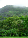 Rain clouds over mountain. Scenic view of monsoon rain clouds over mountain with green trees in foreground Royalty Free Stock Images
