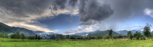 Rain clouds over mountains. Panoramic view of dark rainclouds over mountain range with green fields in foreground royalty free stock image
