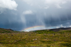 Rain clouds and rainbow with volcanic landscape of moss and rocks, Krafla area, Iceland Stock Image