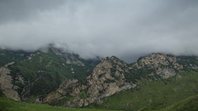 Rain clouds slowly cover the stony mountain slopes. the lush green of the local meadows slope of the Caucasus mountains. stock video footage