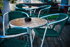 After the rain. Coffee tables and chairs on a terrace after the rain in Houlgate, Calvados, France. An ashtray is on the table Royalty Free Stock Images
