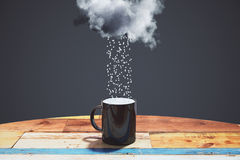 Rain comes from the cloud into black cup on the wooden table at Royalty Free Stock Photography