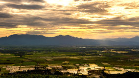 Rain curtaining a view of the mountains.Rain storm over Rice fie Royalty Free Stock Photos