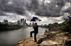 Rain Dance. A businessman in a suit dances with an umbrella in his hand while standing atop a rocky cliff overlooking the city opposite him Royalty Free Stock Images