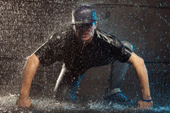 Rain dancer. Man crouched down in rain Royalty Free Stock Images