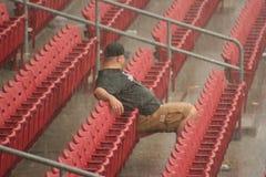 Rain Delay. Man sits out rain delay Stock Photography