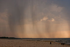 Rain in the distance. Dark rain clouds sending sheets of rain down in the distance. Rain on the sea, a view from a beach stock photography