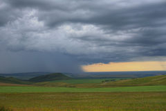 Rain on a distant plane. And fileds and hill Royalty Free Stock Photography