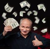 Rain of dollar bills. Lucky old man holding with pleasure group of dollar bills Stock Photos