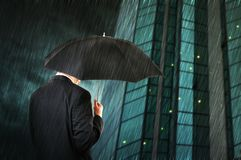 Rain down. Businessman is walking toward a corporate building, holding an umbrella. Hard rain fallin Royalty Free Stock Photography