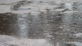 Rain dripping through the puddles. Raindrops. Heavy rain dripping through muddy puddles city stock footage