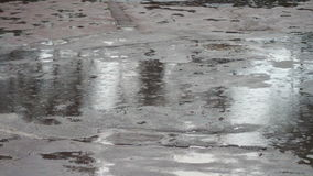 Rain dripping through the puddles. Raindrops. Heavy rain dripping through muddy puddles city stock video footage