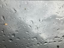 Rain drop on glass. With black cloud background Stock Photos