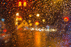 Rain drop with street colorful traffic lights at night blur bokeh abstract background. Concept for background Stock Images