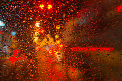 Rain drop with street colorful traffic lights at night blur bokeh abstract background. Concept for background Stock Image