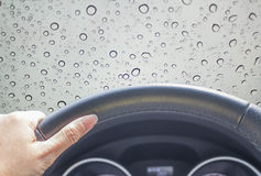 Rain drop on window. Hand of woman driving car with abstract water drop on mirror Stock Photography