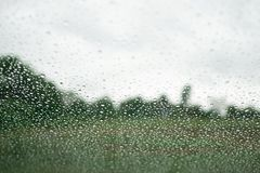 Rain drop on the window with tree and sky background. Use for background Stock Photos
