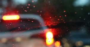 Rain drop on windshield drive car in the city street. Drive car in the city street with rainy day weather, rain drop on windshield with blur light of vehicle on stock video footage