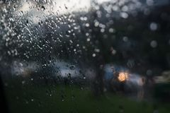 Rain droped on the window. Rain drops on window glasses surface with cloudy background. Natural pattern of raindrops isolated on cloudy background. Sky as a Stock Image