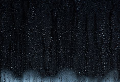 Rain droplets running down a window, abstract background Royalty Free Stock Photos