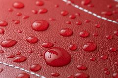 Rain drops. On red leather with umbrella reflection Royalty Free Stock Photography