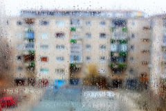 Rain drops. Are seen on a window with apartment flats in the background Stock Photo