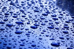 Rain drops on blue car body, shallow focus royalty free stock photography