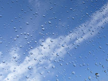 Rain drops and blue sky. A view of raindrops on the glass of a window with blue sky in the background Royalty Free Stock Photo