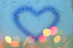 Rain drops and blurred heart write on window with light bokeh. Royalty Free Stock Photos