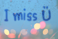 Rain drops and blurred heart write on window with light bokeh. Stock Photo
