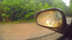 Rain drops on car side view mirror and window. This is a shot from inside of a car of rain drops falling onto car side view mirror and window somewhere at forest stock video