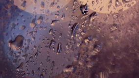 Rain drops on a car window, blured traffic lights on background. stock video footage