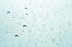 Rain drops on car window in cyan tone with blur effect. Abstract background and texture Stock Photography