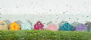 Rain drops on a car window looking at beach huts Stock Photography