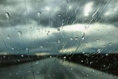 Rain drops on a car windshield. Rainy day view through a car window. Rainy season concept Royalty Free Stock Image