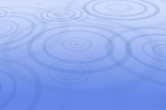 Rain drops creating ripples in water Stock Photos