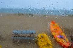 Rain drops drip down window of beach hut. Royalty Free Stock Image
