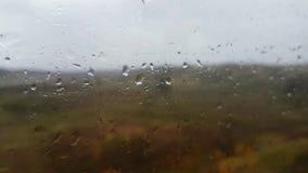 Rain drops drip onto the glass of the train. Rain drops drip onto the glass of the moving train stock footage
