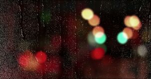 Rain drops falling down on glass with multi color city car traffic bokeh light background, water droplets on window glass. Or car glass stock video footage