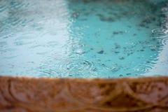 Rain drops falling into the fountain Royalty Free Stock Image