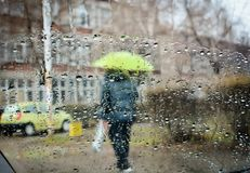 rain drops during falling rain and blurred man with umbrella royalty free stock image