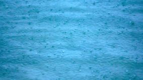 Rain drops falling on sea surface nice blue color. Royalty Free Stock Photos